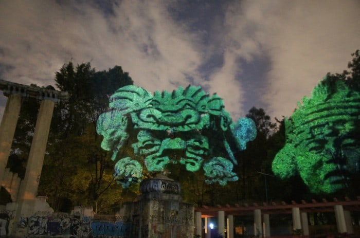 Dioses del Maíz (Corn Gods): Prehispanic 3D Gods projected on trees against transgenic corn.