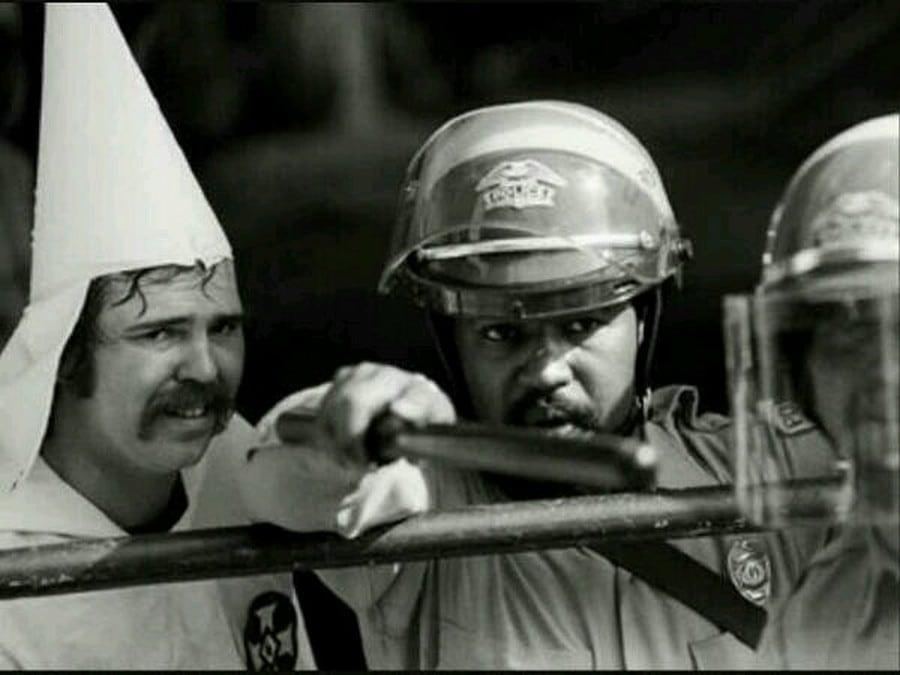 Black officer protecting KKK member from protesters, 1983