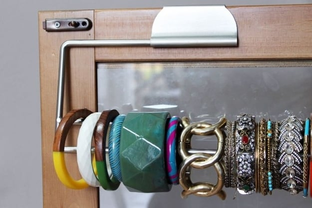 Display bracelets on a paper towel holder to keep them organized.