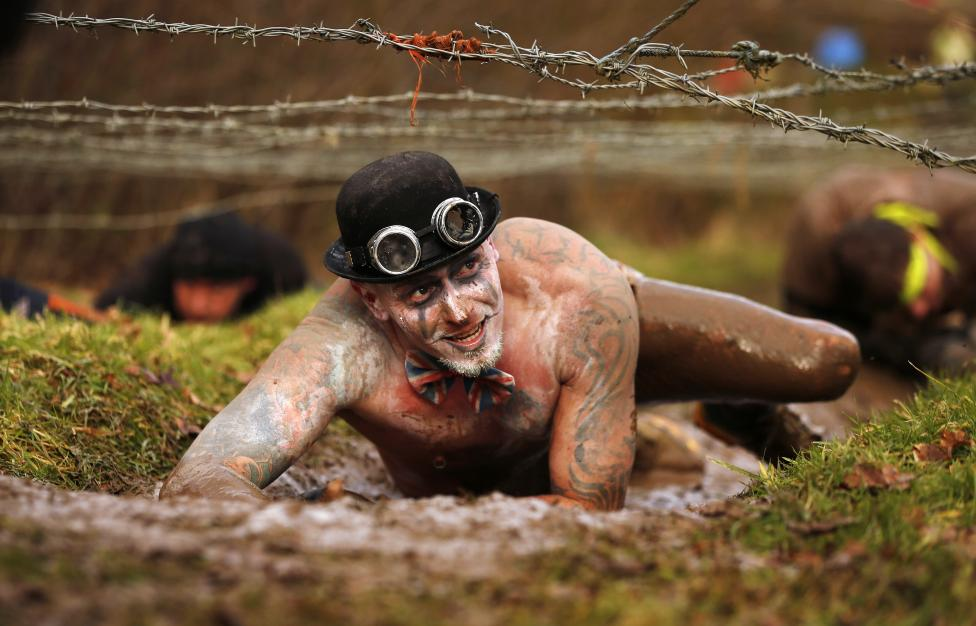 A competitor crawls beneath barbed wire during the Tough Guy event in Perton, central England