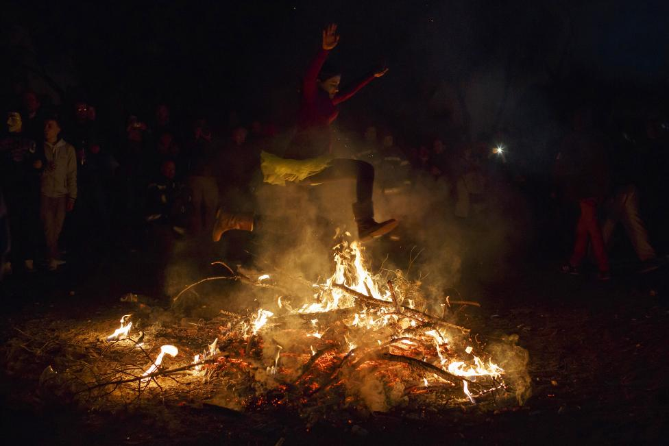 "A girl jumps over the fire during the ""The Burial of the Sardine"" funeral procession, which marks the end of carnival festivities, in Madrid"