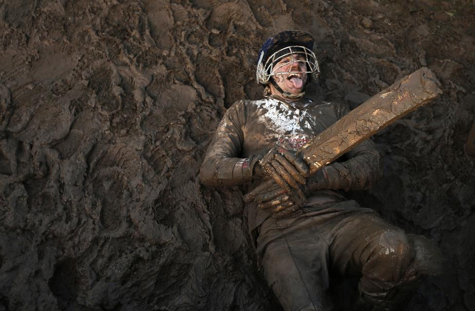 A competitor dressed as a cricketer lies in the mud during the Tough Guy event in Perton