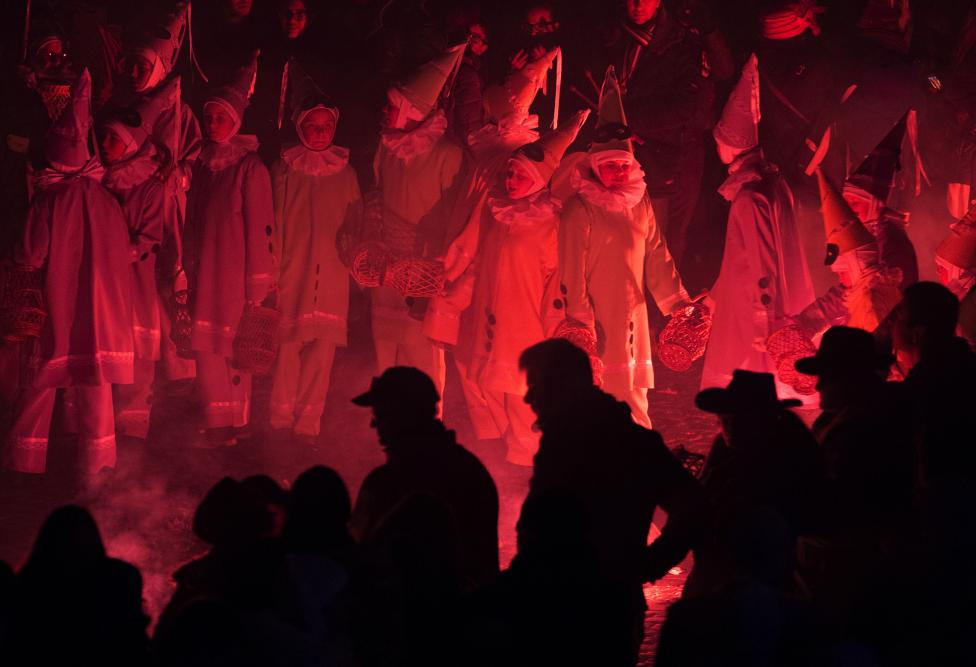 Children dressed as Pierrot dance around flares during the Rondeau at the Carnival event in Binche