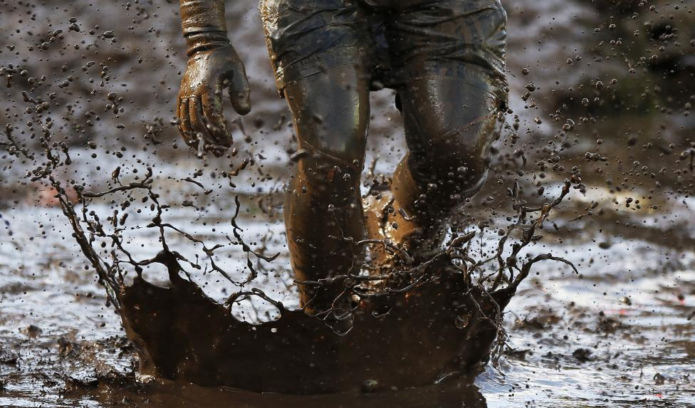 A competitor runs through mud during the Tough Guy event in Perton, central England
