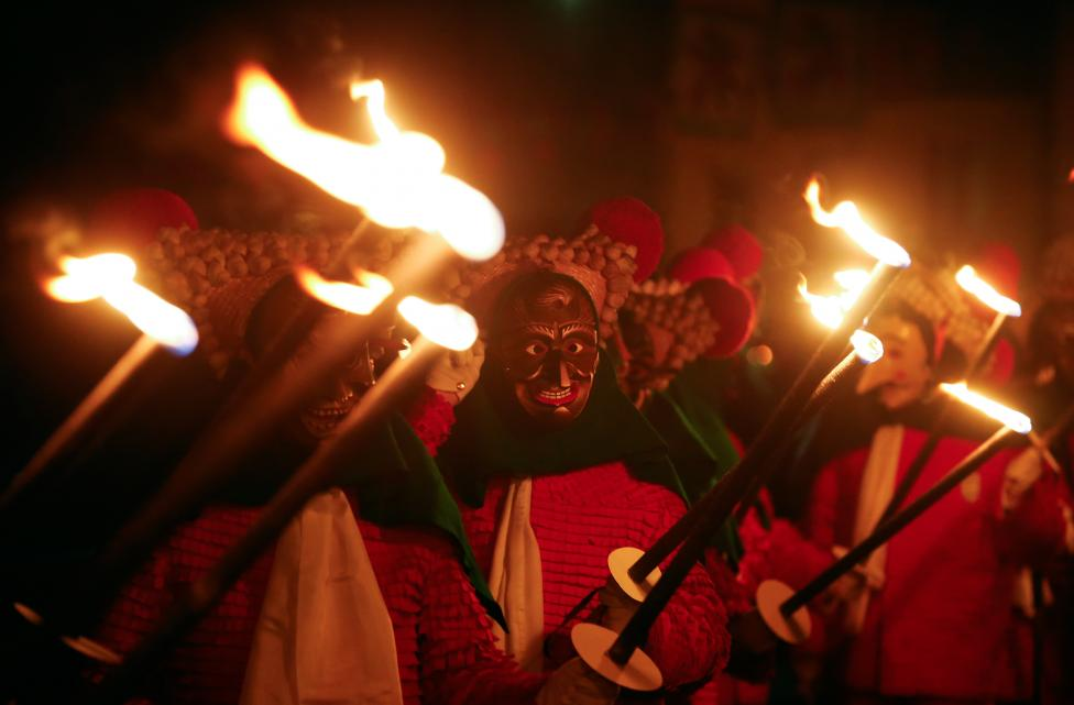 Revellers in traditional costumes and carnival masks parade through the village of Elzach in the Black Forest