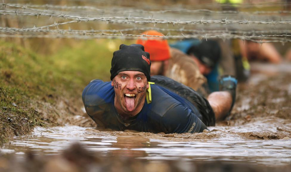A competitor gestures as he crawls beneath barbed wire during the Tough Guy event in Perton, central England