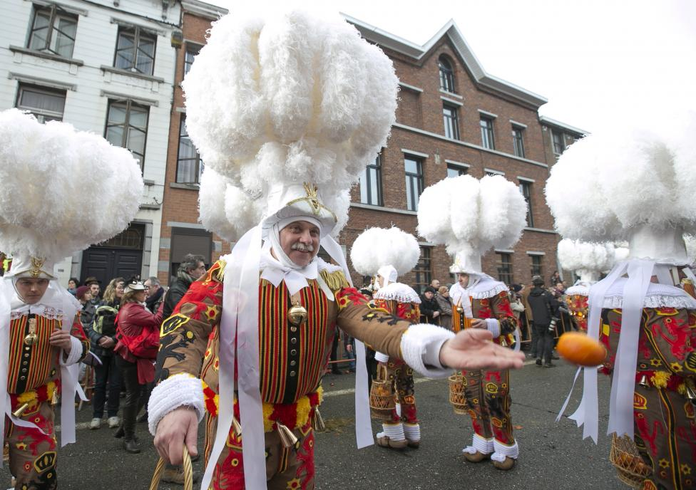 Gille of Binche throws an orange while taking part in the parade during the carnival event in Binche