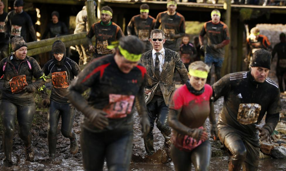Competitors run through mud during the Tough Guy event in Perton, central England