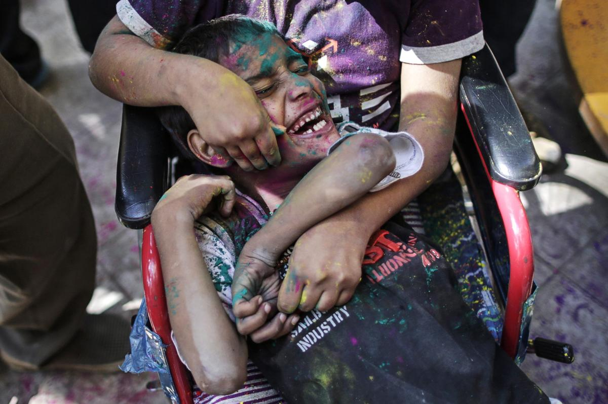 Children covered in colored powder played during celebrations of Holi at the Society for the Education of the Crippled in Mumbai on March 4. (Danish Siddiqui/Reuters)