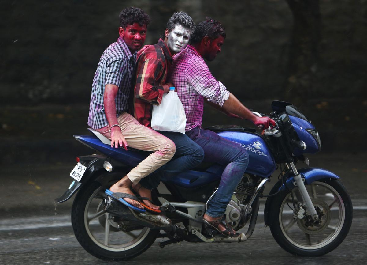 Indian men, their faces smeared with colored powder, rode a motorbike during Holi in Hyderabad, India, on March 6. (Mahesh Kumar A/Associated Press)
