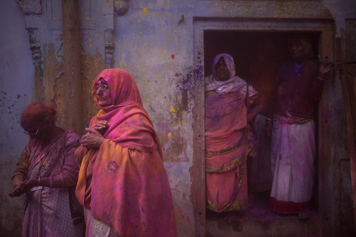 Indian Hindu widows stood covered with colored powder after celebrations marking Holi at the Pagal Baba Ashram in Vrindavan, India. (Tsering Topgyal/Associated Press)