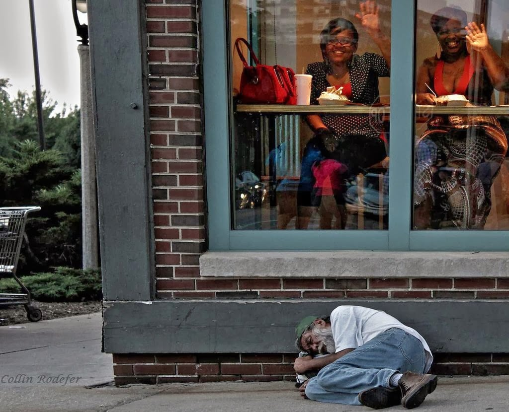 Ignorance is bliss – Homeless man sleeps outside a diner in Milwaukee.