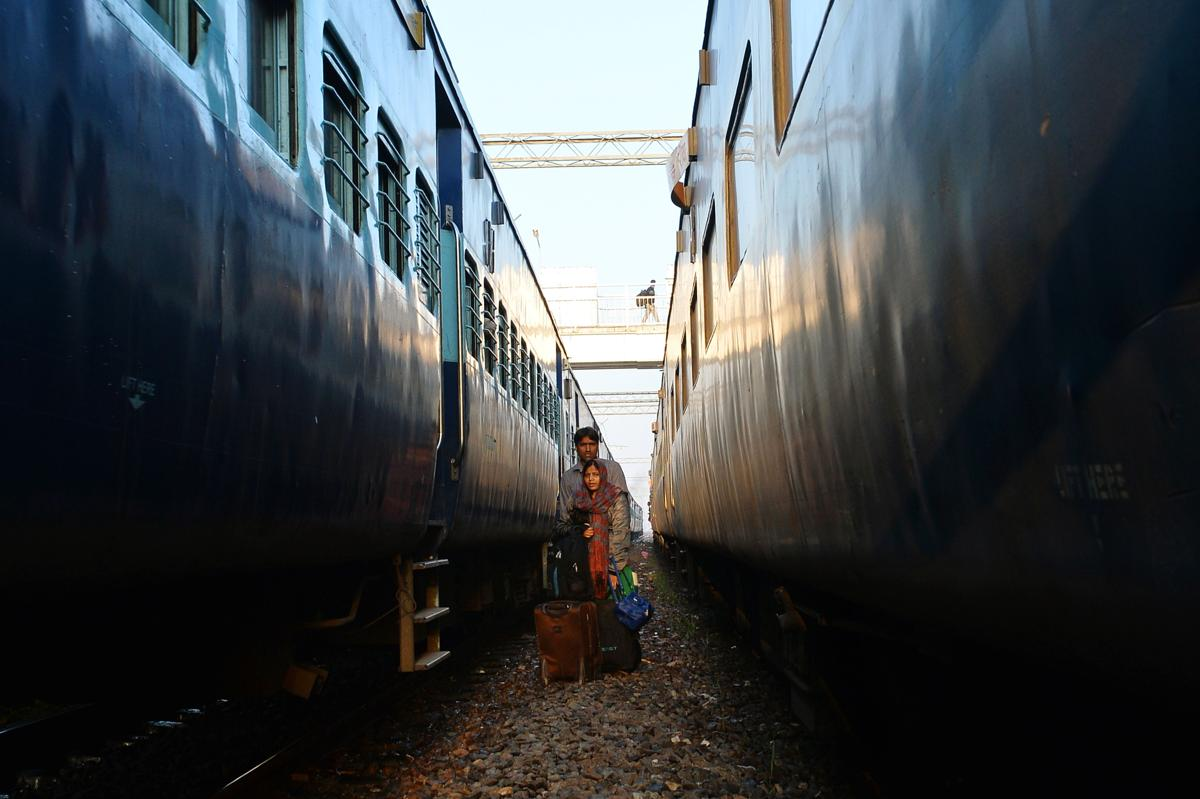 An Indian married couple stood waited to cross the railway tracks on arrival in their hometown for festival holidays in Allahabad on March 6. Indian Railways runs special trains to meet the demand for travel during the Holi Festival. (Chandan Khanna/AFP/Getty Images)