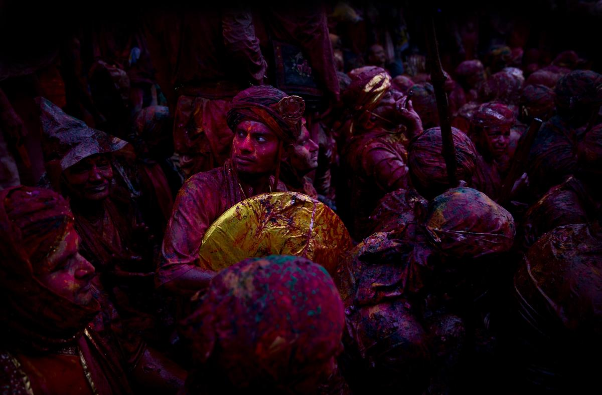 Indian Hindu devotees smeared with colors visited the Nandagram temple, famous for Lord Krishna and his brother Balram, during Lathmar Holi festival in Nandgaon, India, on Feb. 28. During Lathmar Holi the women of Nandgaon, the hometown of Krishna, beat the men from Barsana, the legendary hometown of Radha, consort of Hindu God Krishna, with wooden sticks in response to their teasing as they depart the town. (Saurabh Das/Associated Press)