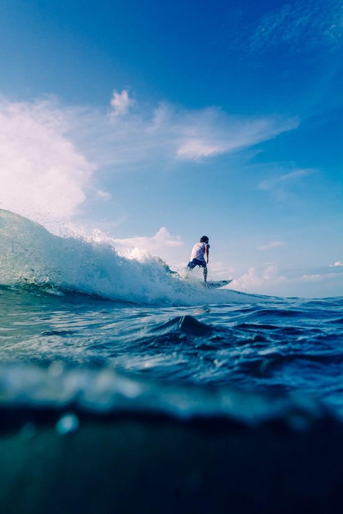 Surfer riding a wave in Uluwatu, Bali