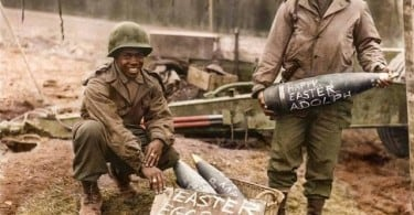 """T/5 William E. Thomas and Pfc. Joseph Jackson prepare a gift of special """"Easter Eggs"""" for Adolf Hitler and the German Army. Scrawling such messages on artillery shells in World War II was one way in which artillery soldiers could humorously express their dislike of the enemy. Easter Saturday, March the 10th 1945, during the Battle of Remagen. (The photographer 1st Lt. John D. Moore of the Signal Corps. Source - US National Archives 111-SC-202330. Colorized by Johhny Sirlande from Belgium)"""