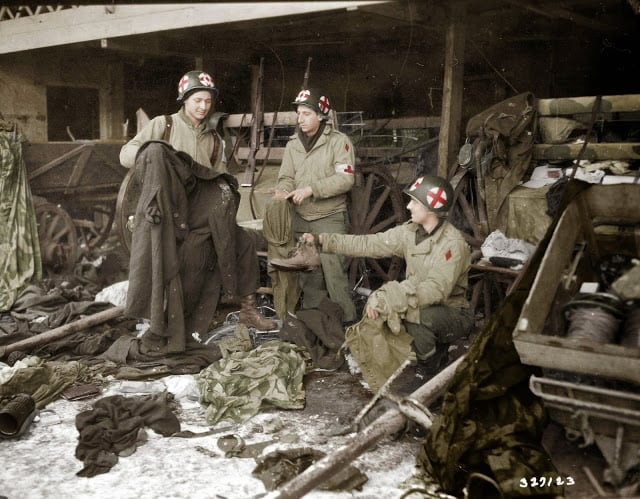 Medics of the US. 5th Infantry Division examining GI clothing found with German-captured equipment after the liberation of the area, near Diekirch in Luxembourg on the 20th of January 1945. (Source - SC-327129 Signal Corps Photo ETO-HQ-45-9223 -Horton. Colorized by Joey Van Meesen from the Netherlands)