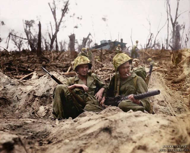 Marine Pfc. Douglas Lightheart (right) cradles his .30 caliber M1919 Browning machine gun in his lap, while he and Marine Pfc. Gerald Thursby Sr. take a cigarette break, during mopping up operations on Peleliu on 14th September 1944. (Colorized by Paul Reynolds. Historic Military Photo Colourisations)