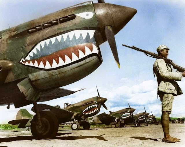 A Chinese Nationalist soldier guards a row of Curtiss P-40 'Warhawks' flown by the 'Flying Tigers' of the American Volunteer Group (AVG). July, 1942. (Source - National Archives and Records Administration - 535531. Colorized by Tom Thounaojam from India)