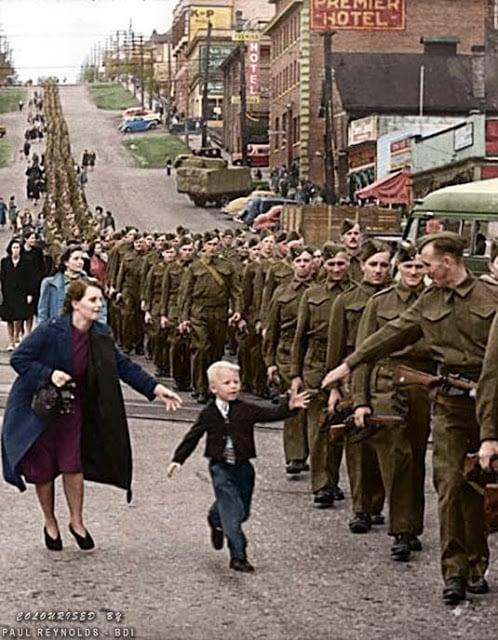 "On October 1, 1940, Private Jack Bernard and other volunteers in The British Columbia Regiment (Duke of Connaught's Own Rifles) were marching smartly down Eighth Street in New Westminster to board a ship and sail off to war. Suddenly, Bernard's five-year-old son broke free of his mother's grasp and sprinted into the military formation to take his smiling father's hand. In that instant, an alert Vancouver Daily Province photographer, Claude Dettloff, snapped the shutter. Soon, his unforgettable image of little Warren ""Whitey"" Bernard was being printed by leading publications throughout North America. It was later used in Canada's war bond drives with the plea, ""help bring my Daddy home."" Jack Bernard survived the war and was reunited with his son in 1945. (Claude Dettloff, photographer - City of Vancouver Archives online database. Colorized by Paul Reynolds. Historic Military Photo Colourisations)"