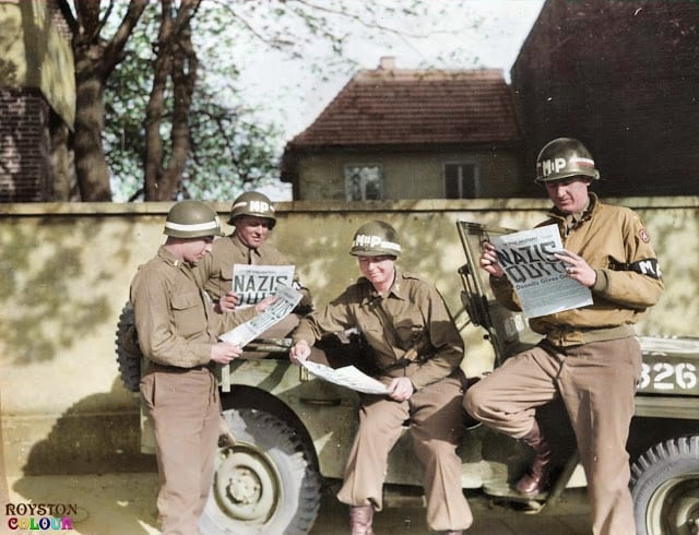 9th Army MPs reading of the surrender in the 'Stars and Stripes' in Germany on the 8th of May 1945. (Source - U. S. Army Military History Institute - Nelson A. Shuey Photograph Collection. Colorized by Royston Leonard UK)