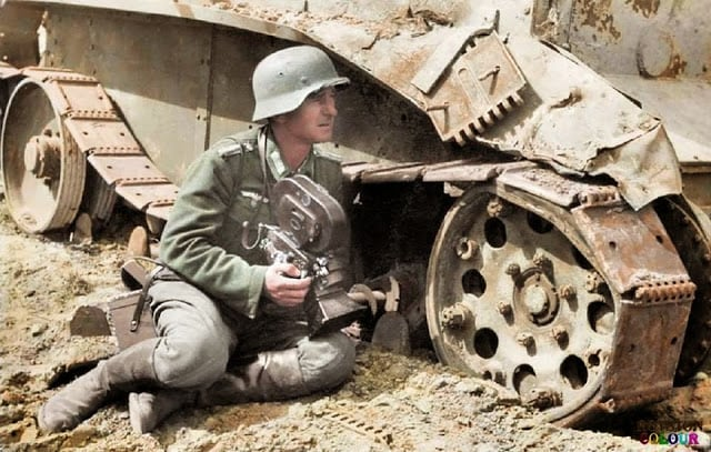 A Kriegsberichter (war correspondent) holding an Arriflex 35 2 1942 camera 35mm ACR 0292 and he is leaning against a knocked out Soviet BT-5 light tank. c.1940/41. (Colorized by Royston Leonard from the UK)