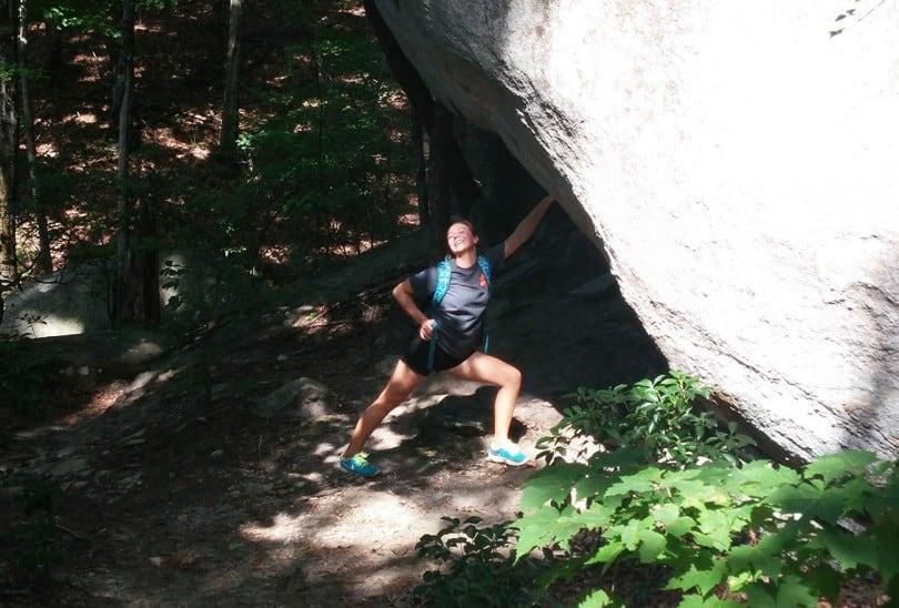 Girl posing beside a boulder while on a trek