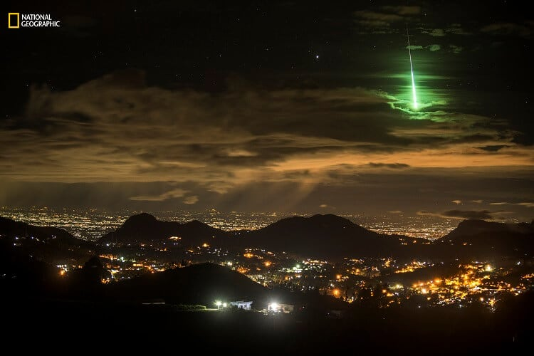 Prasenjeet Yadav/2016 National Geographic Nature Photographer of the Year. Serendipitous Green Meteor. Honorable Mention—Landscape: Anand Varma was visiting me and I was showing him around a mountain range in South India called the Western Ghats. We camped on the side of a road and I set up my Nikon D600 and a 24-70mm lens to take 15-second exposures. I set the camera to take 999 images. I slept next to the camera and it continued taking pictures until dawn. It wasn't until the next afternoon that I reviewed my images and noticed something unusually bright and green. I showed it to Anand, and we realized that I had captured an extremely rare event. After checking with a few experts, I learned that it was a green meteorite, and getting it on camera is very rare. This is an example of being at the right place at the right time to capture something totally unexpected. For those 15 seconds, I was the luckiest photographer on the planet.