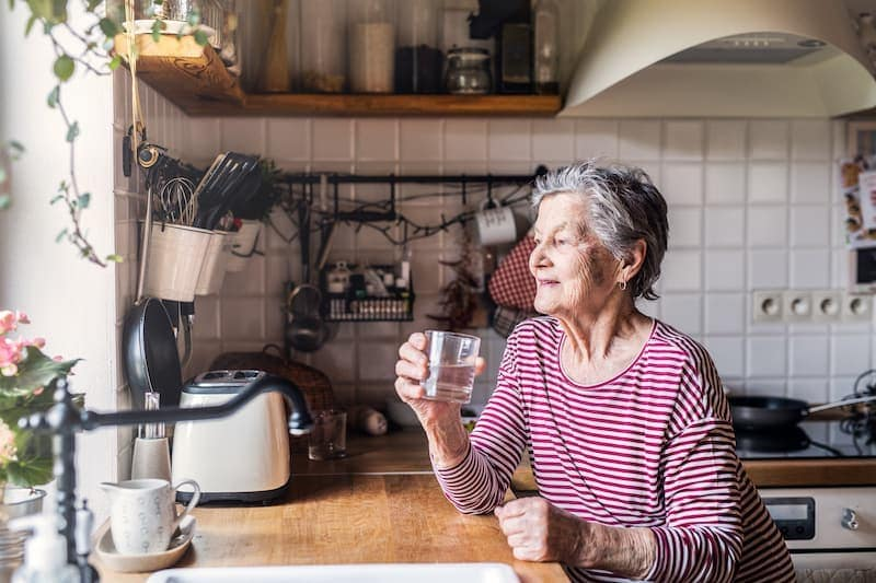 an elderly woman standing in the kitchen holding TZL6XPE