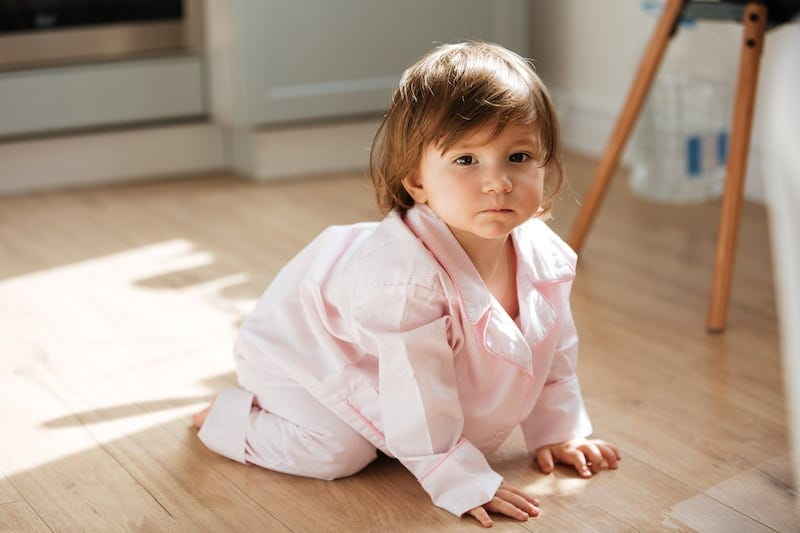 beautiful little girl in pajamas on wooden floor PT3T7WC