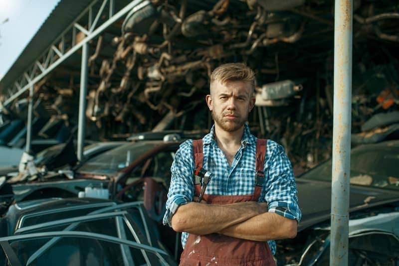 male mechanic at the stack of cars on junkyard VCJZGMK