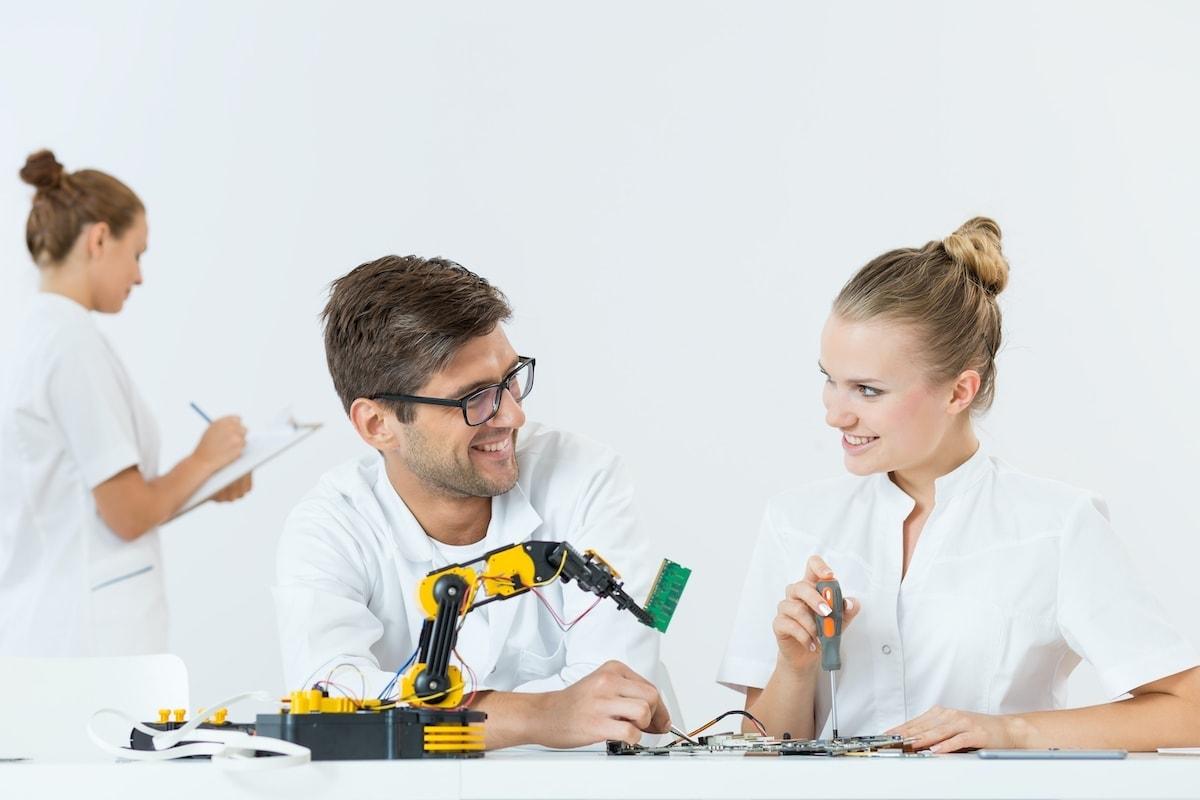 man and woman using a robotic arm PQDWLFJ