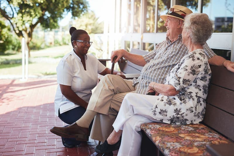 retired couple relaxing outdoors with female PVG5N76