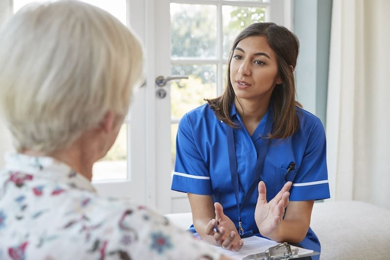 senior woman talking to young care nurse on home P3MELDH