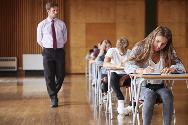 teenage students sitting examination with teacher P4NE2VS