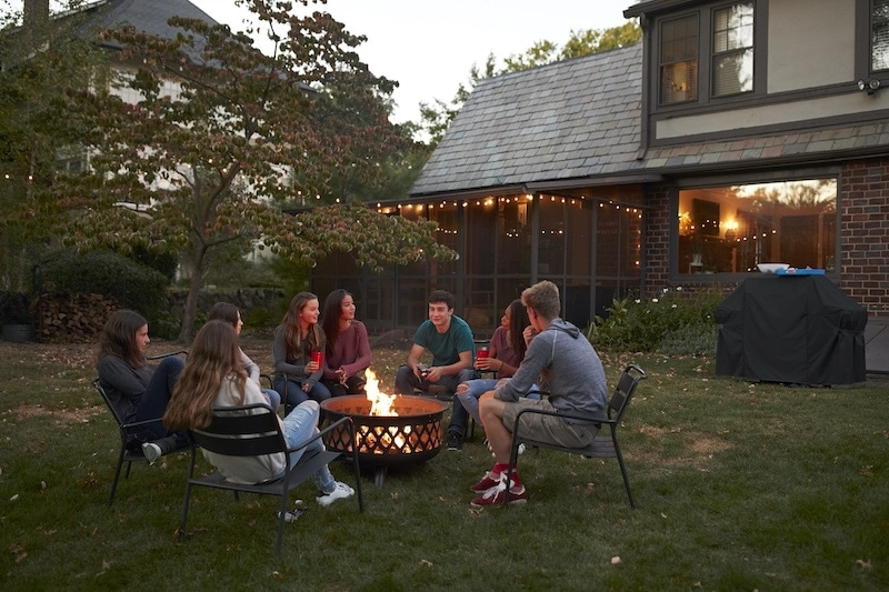 teenagers sit talking around a fire pit in a P7DKRBC