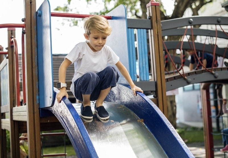 young boy playing slide in playground PREAP84