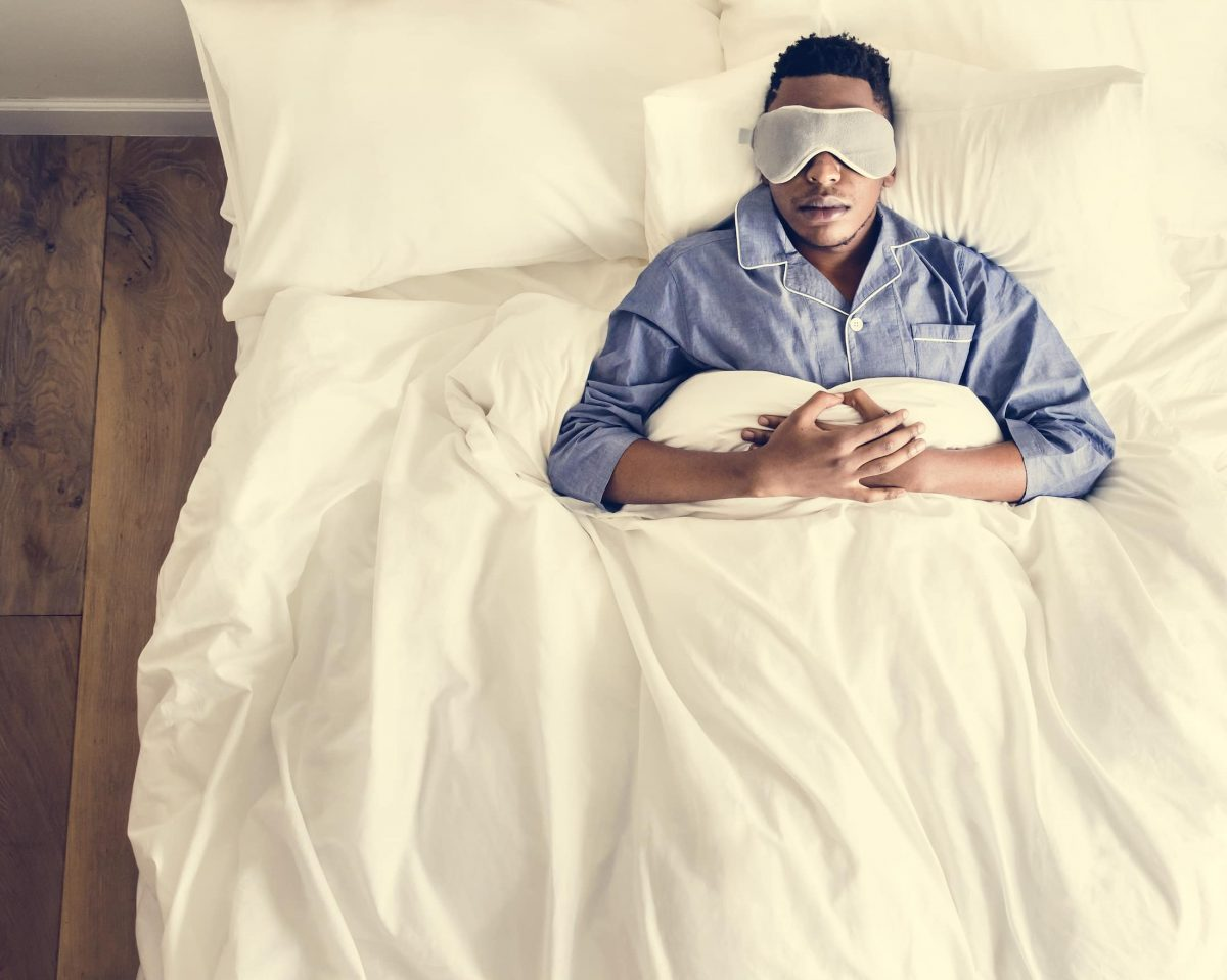 black man sleeping on bed with eye mask PFU8VYD