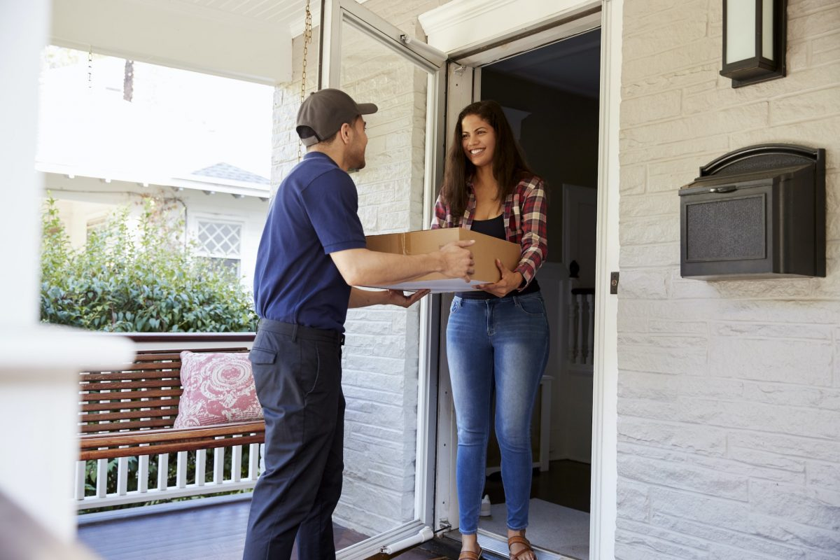 courier delivering package to woman at home PR78SK6