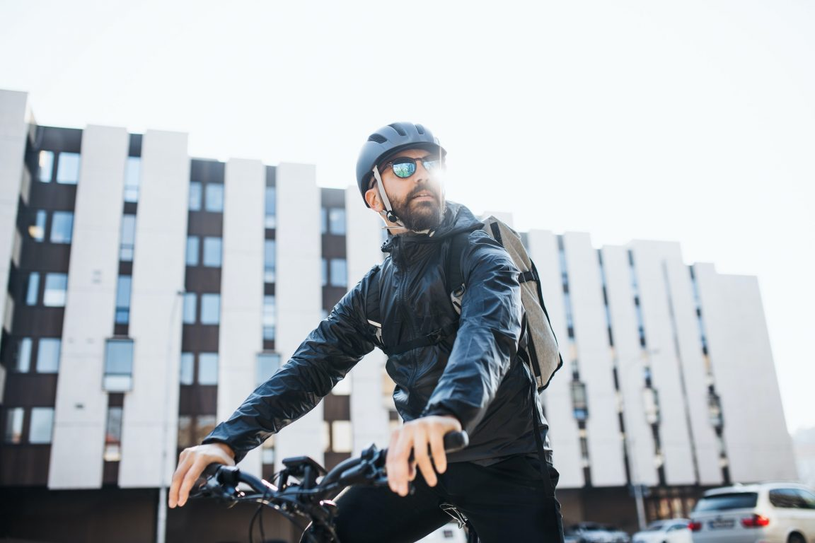 male courier with bicycle and sunglasses KXZS6UN