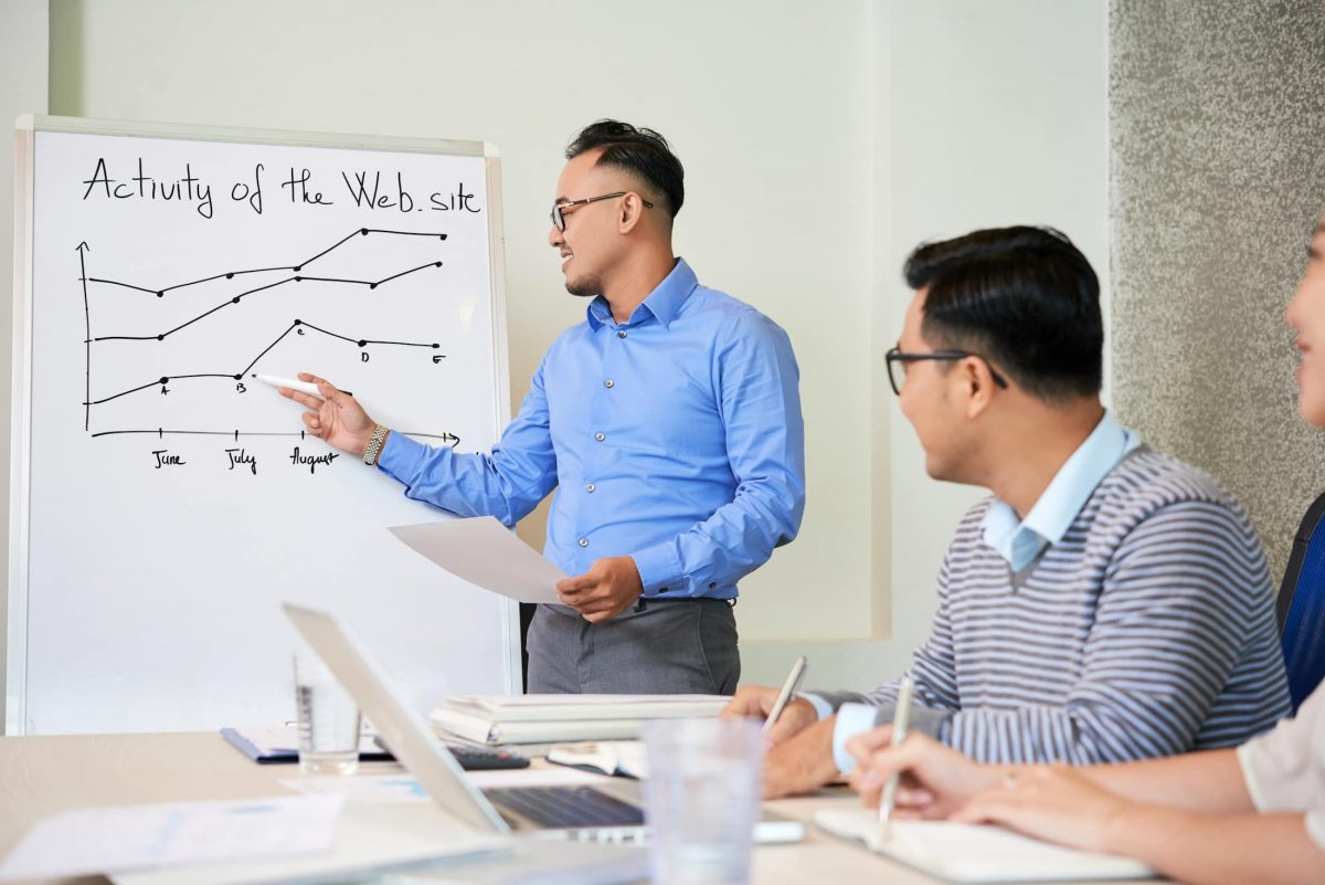 man showing growing chart on presentation for 89KMXCY