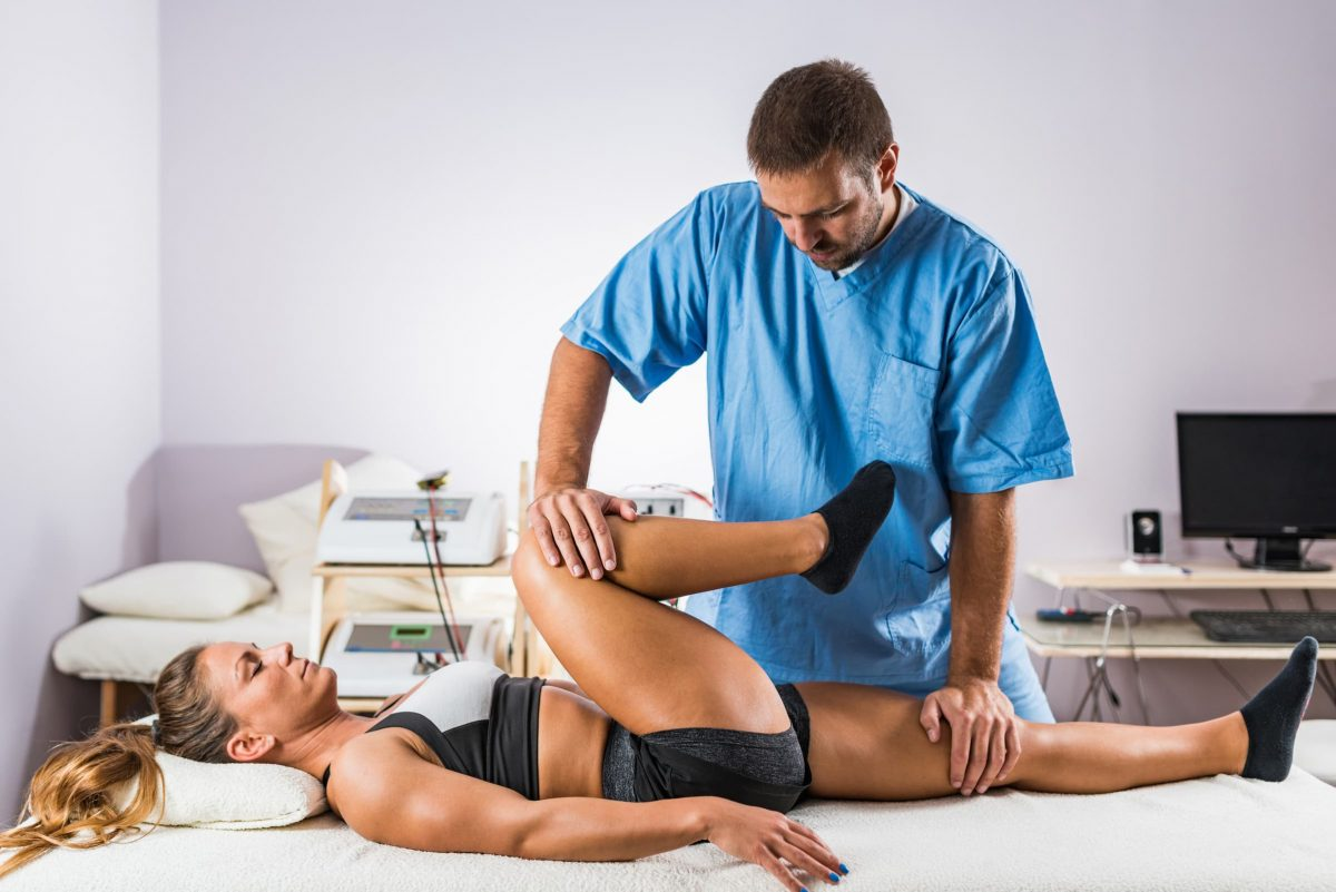 physical therapy therapist working with female P6GYQZK