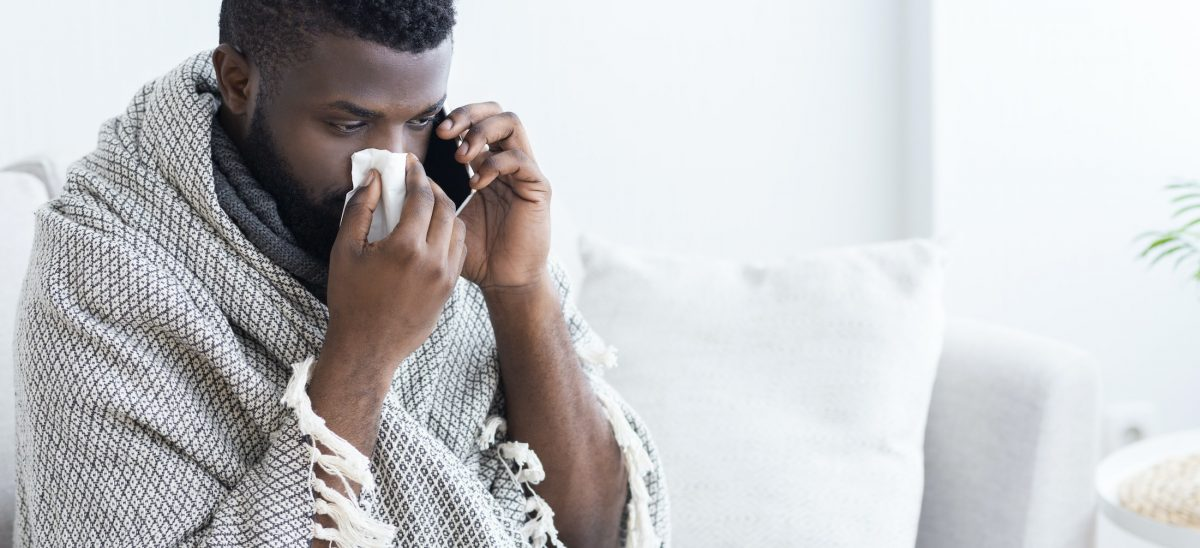 sick black man calling on phone to doctor CLF5T9J