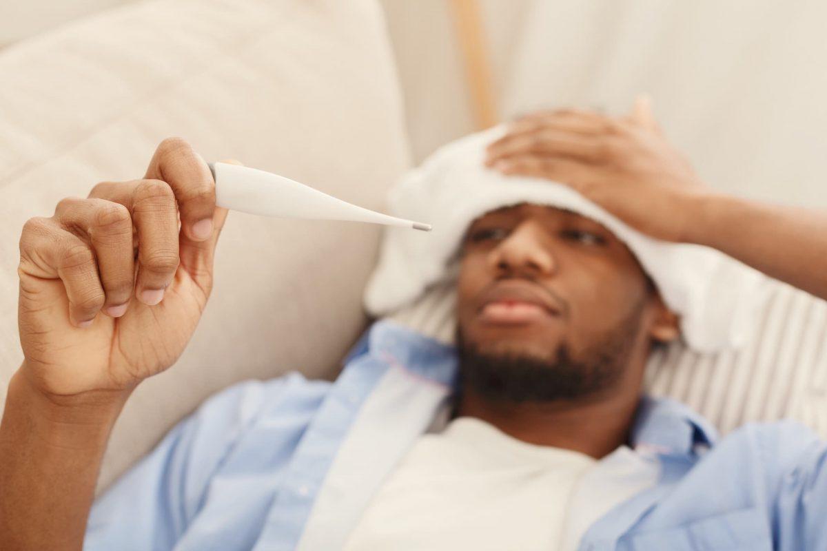 sick black man checking his temperature at home KT26PRE