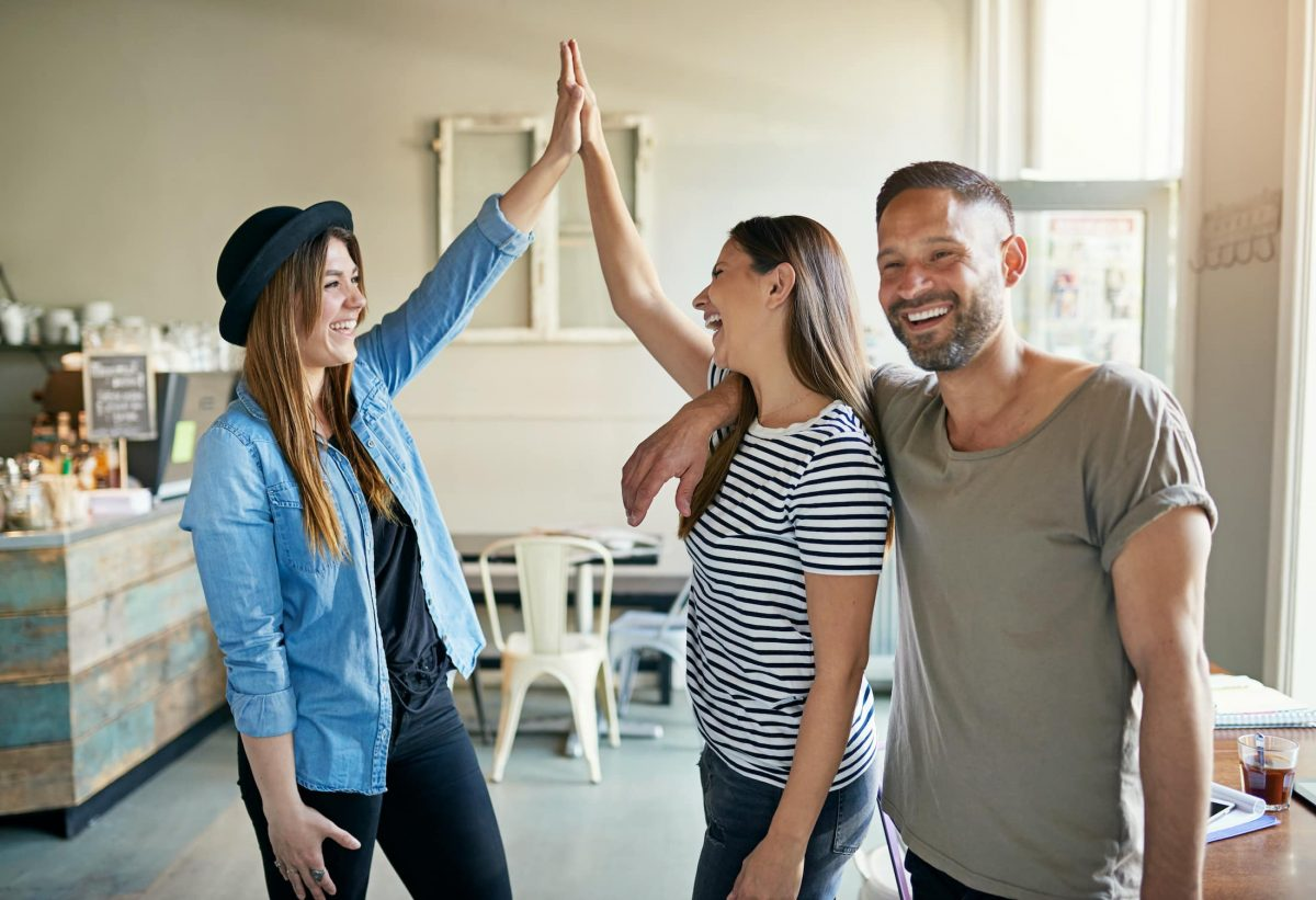 two women putting up high fives with male friend VE4A349
