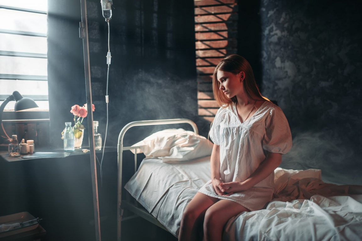 young sick woman sitting on hospital bed on drip PNZVWG6