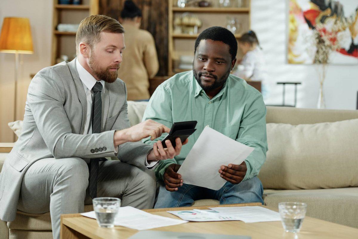 diverse men calculating loan rate AWEYJTR