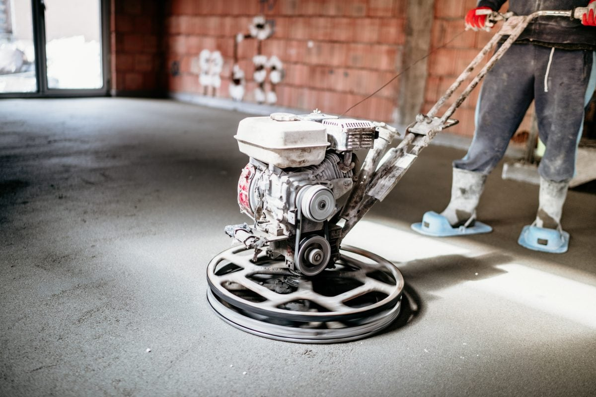 worker with power trowel tool finishing concrete YQXPGEG