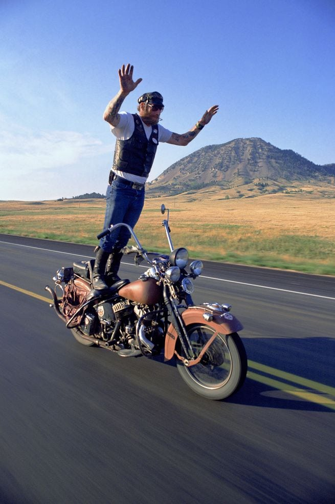 """I have photographed quite a few bikers surfing like this, but in this frame, Puppy exudes the spirit of what biking is all about as he rides past Bear Butte. A friend of mine captured that spirit when she looked at this image and said, """"Feel the Freedom""""."""