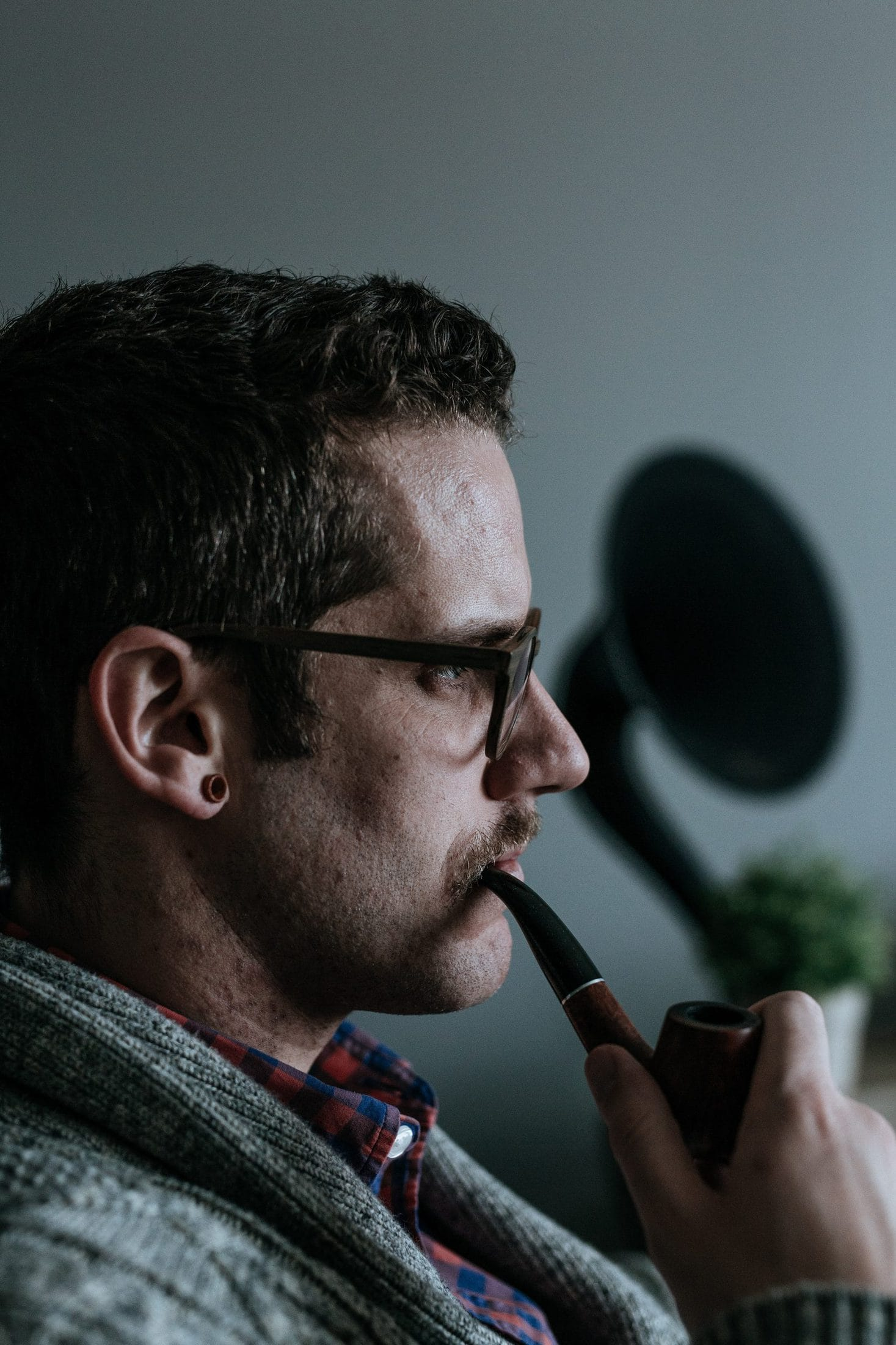 man holding tobacco pipe